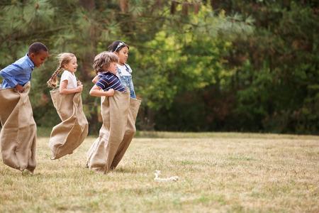 saltar: Niños en una carrera de sacos compitiendo entre ellos en verano Foto de archivo