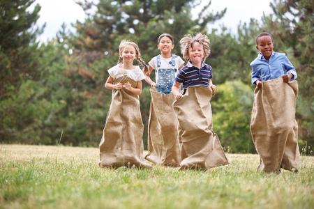 Kinderen plezier op zaklopen in het park Stockfoto