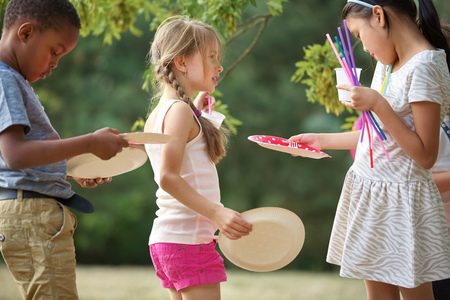 birthday party kids: Interracial group of kids distribute plates at a birthday party