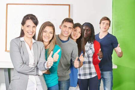 profesor alumno: Interracial group of pupils and their teacher hold their thumbs up