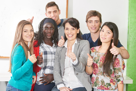 Interracial group of students with teacher holding their thumbs up