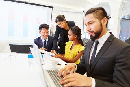 Homme d'affaires à une réunion avec travail d'ordinateur portable et de l'écriture