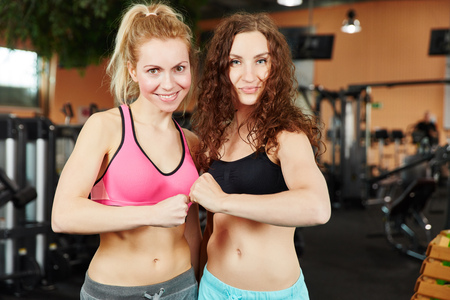 Two motivated women at fitness center clentching their fists