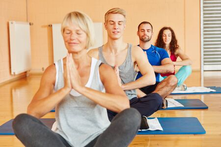 meditates: Group meditates and relaxes in yoga class at fitness center