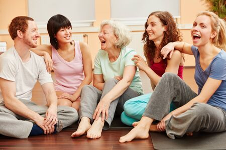 Senior woman full of vitality and group happily laughing at fitness center photo