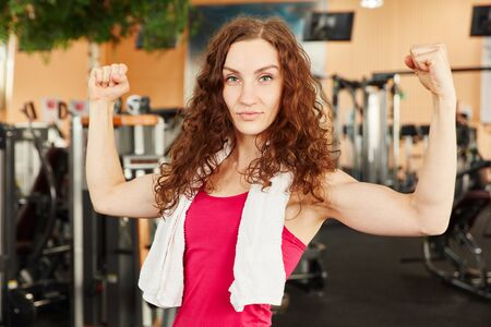 Sporty woman showing her muscles at the gym Stock Photo