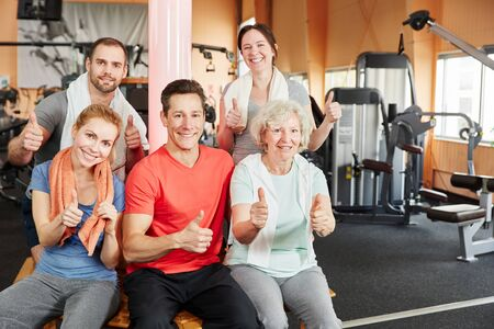 Successful group of people and senior woman holding thumbs up at the gym photo