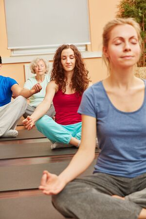 Women meditating in yoga class for relaxation photo