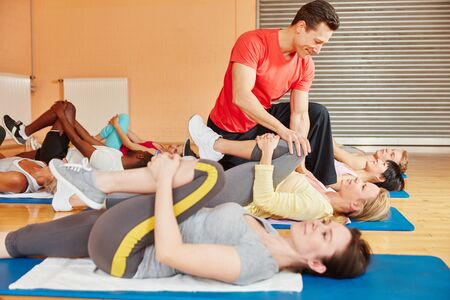Coach in fitness class showing stretching exercise and helps woman at fitness center photo