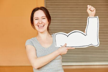 Woman laughing and showing false muscles at the gym Stock Photo