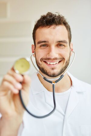 auscultate: Physician with stethoscope smiling friendly