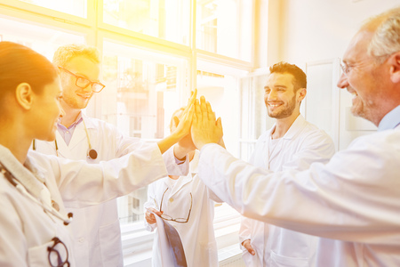 staff de medicos: Team giving High Five during medical meeting as motivation