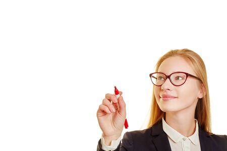 Woman wearing glasses in a suit writing with a red pen