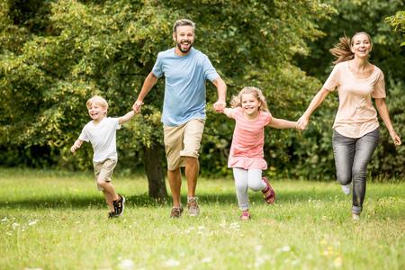 Gelukkige familie met twee kinderen samen in het voorjaar in het park