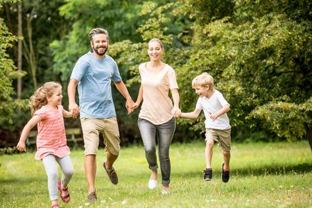 Gelukkige familie samen in de zomer rennen in de natuur