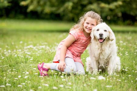 Ragazza e cane come amici felici insieme in estate nella natura Archivio Fotografico - 74740335