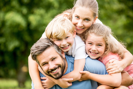 Happy family with two kids hugging together in harmony in garden