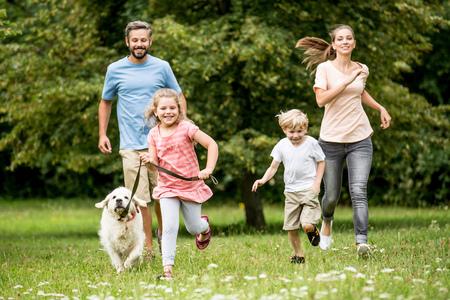 Felices los niños y los padres con el perro como familia corriendo en la naturaleza