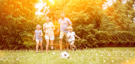 Family with soccer ball in summer playing and having fun Archivio Fotografico