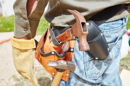 Carpenters tool belt with hammers at construction site Stock Photo