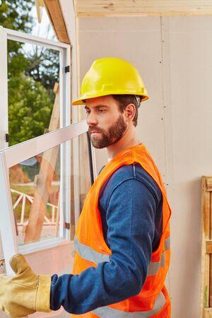 housebuilding: Window builder working on mount of new installation Stock Photo