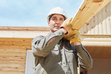 housebuilding: Blue collar worker carrying wood in construction site