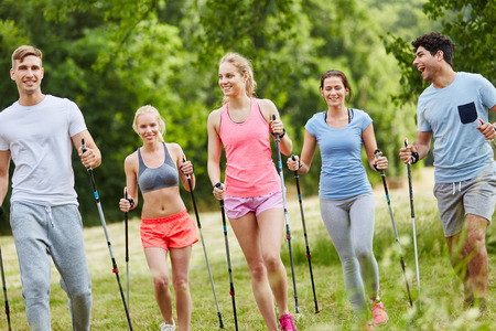 Group of active people nordic walking as training in the nature