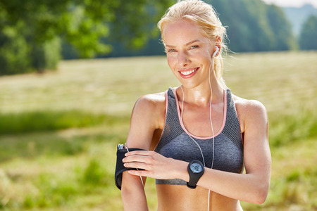 Woman as jogger with wearables for music and training Stock Photo