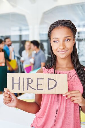 Young african business woman as trainee in start-up holding hired sign Stock Photo