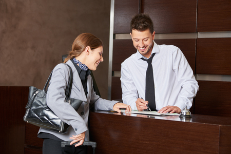 Man at hotel reception giving advice to woman with city map
