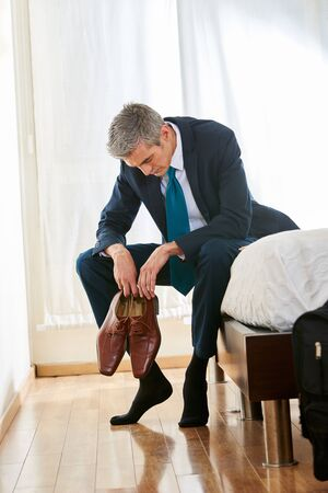 burned out: Tired businessman in hotel room sitting on bed with his shoes in his hands Stock Photo