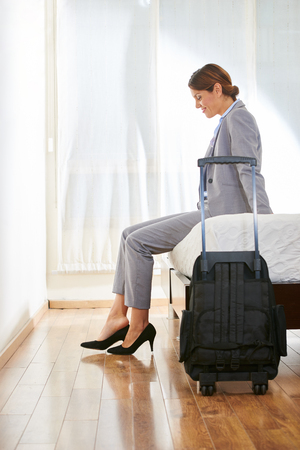 Geschäftsfrau mit Koffer sitzt auf dem Bett in einem Hotelzimmer Standard-Bild
