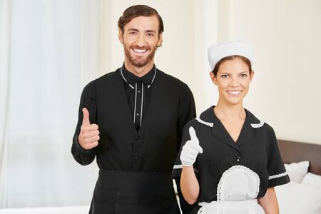 hotel staff: Hotel clerk and maid holding thumbs up as service team in hotel room