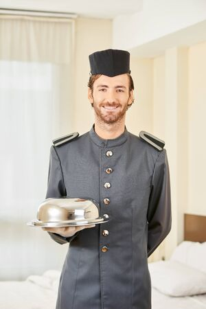 delivery room: Page in hotel serving food with cloche in hotel room Stock Photo