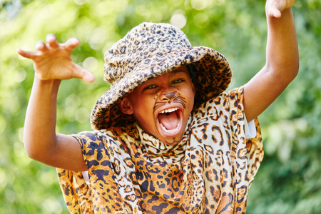 Child with carnival costume plays leopard in creative school play
