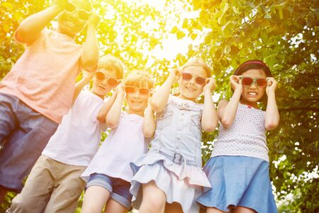 cool kids: Cool group of kids as interracial friends with sunglasses in summer Stock Photo