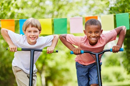 suspenso: Two children with scooters as friends stand with ambition before race