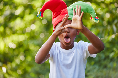 nonsense: Creative child as harlequin playing and making funny signs in carnival Stock Photo