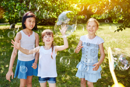 Children playing with soap bubbles in summer at the park