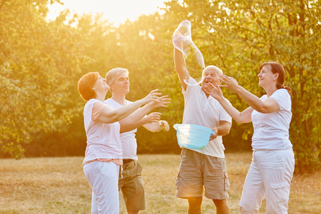 Group of senior citizens making soap bubbles and having fun in the park Stock Photo