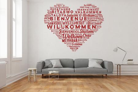 Willkommen in vielen Sprachen in Herzform als Wandaufkleber im Wohnzimmer (3D Rendering)