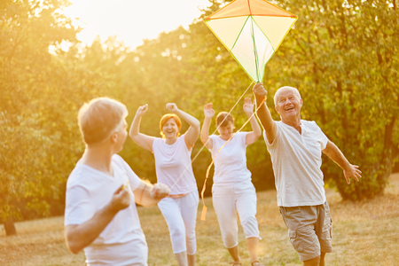 Seniors laughing and running while flying a kite Stock Photo
