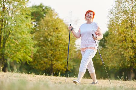 Glückliche ältere Frau , die mit Wanderstöcken in der Natur wandert