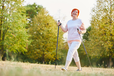 Happy senior woman hiking with hiking sticks in the nature