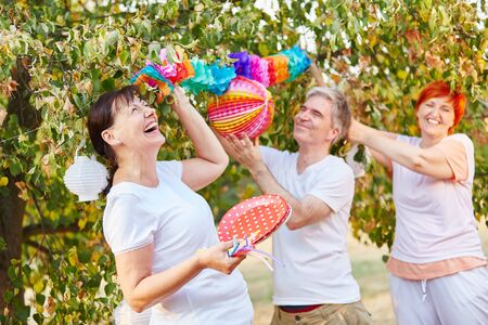 Seniors laughing and having fun while decorating for a birthday party in the park