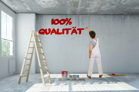 journeyman: Painter writing German slogan 100% Qualitaet (100% quality) on a wall