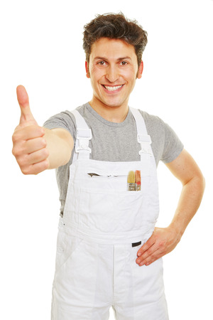 Happy painter in white overall holding thumbs up Stock Photo