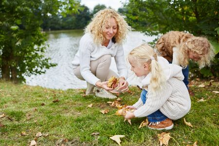Woman and children collecting leaves as a family in the fall