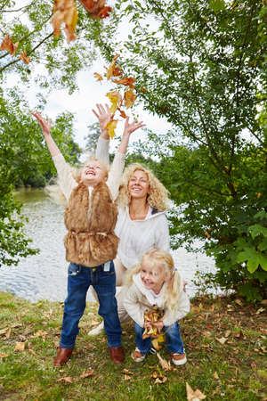 romp: Children run and play in the fall with leaves and have fun