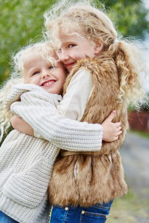 Two girls hugging each other as sign of sibling love and affection